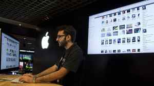 An employee at an Apple store checks the iTunes store on a computer as he works in Sao Paulo, Brazil, Tuesday Dec. 13, 2011. Apple says it launched iTunes on Tuesday in Brazil and 15 other Latin American countries.