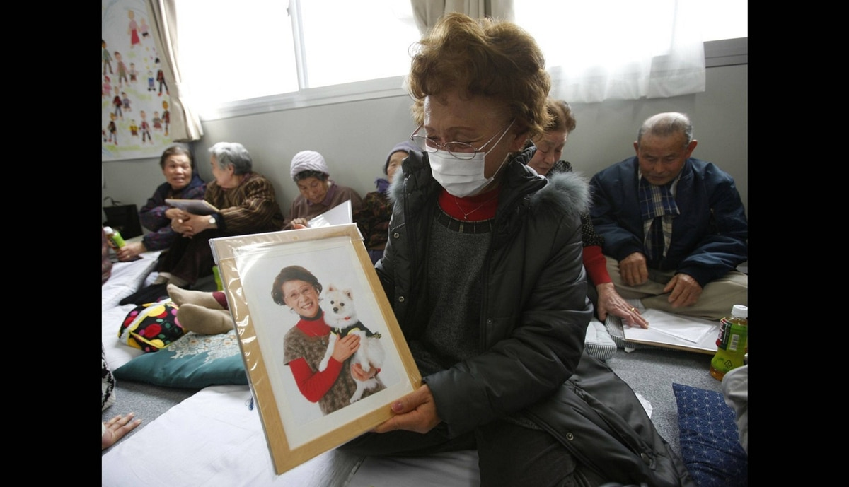 Katsuko Abe, 71, looks at her framed portrait after receiving it from 3.11 Portrait Project volunteers at the Midorigaoka temporary shelter in Koriyama, Fukushima prefecture in the Tohoku region, February 27, 2012. The project was conceived by photographer Nobuyuki Kobayashi who takes portraits of Japan's earthquake survivors. The portraits are then sent to schoolchildren from non-disaster areas, who frame the portraits and send them back to the survivors along with personal messages of support.