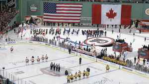 The Philadelphia Flyers, left, and Boston Bruins, right, stand for the national anthems before the New Year's Day Winter Classic NHL hockey game on an outdoor rink at Fenway Park in Boston, Friday