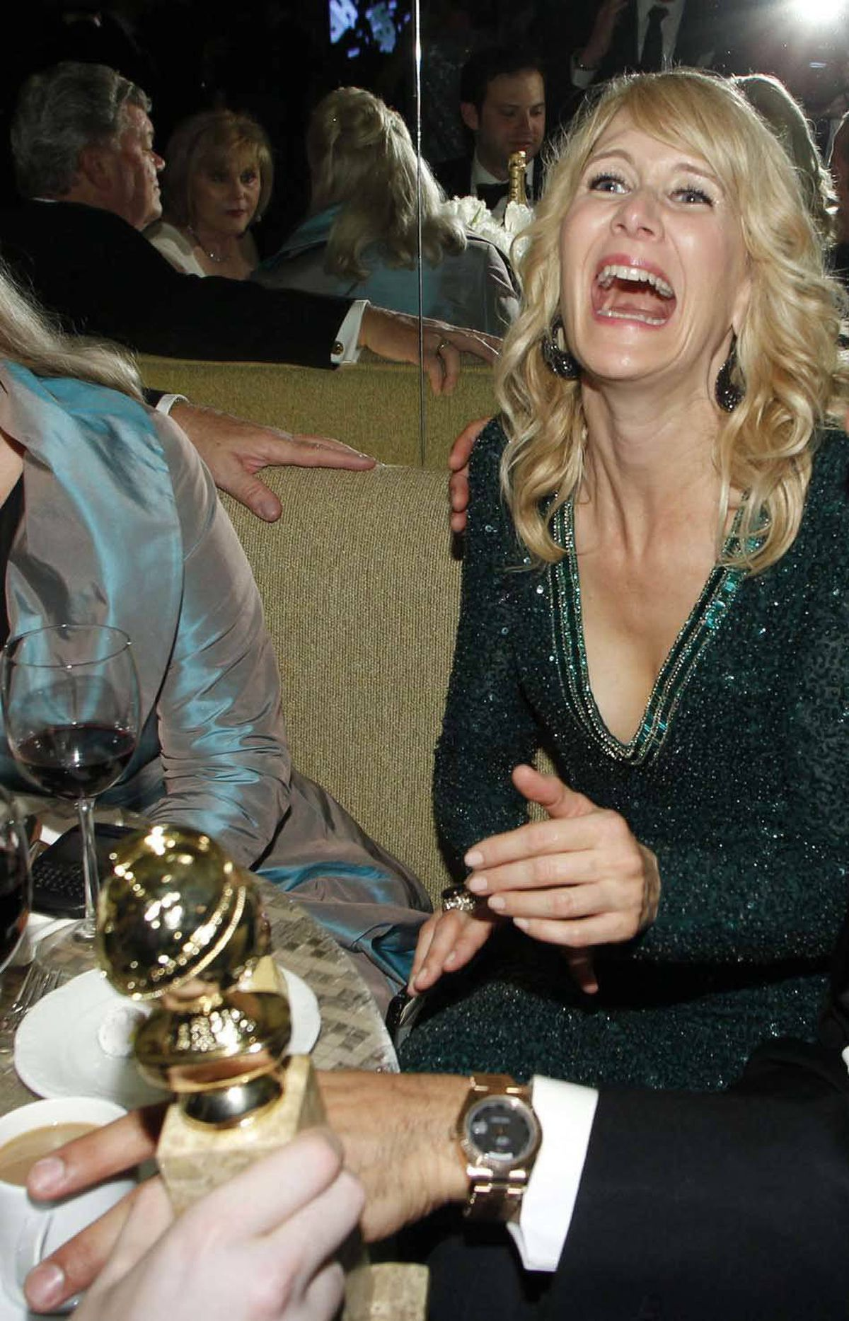 Laura Dern, who moments earlier was seen talking to Gerard Butler, agrees to try and fit her Golden Globe award in her mouth at the HBO after-party in Beverly Hills Sunday night.