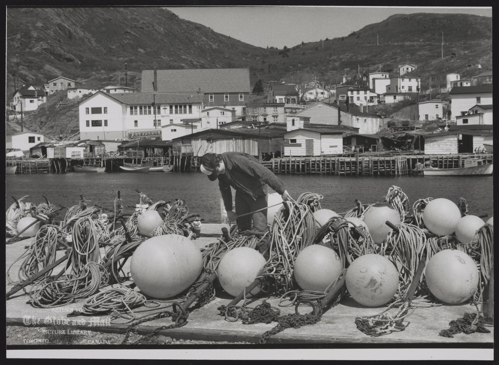 NEWFOUNDLAND prov. Misc. Fishermen preparing nets in Petty Harbour