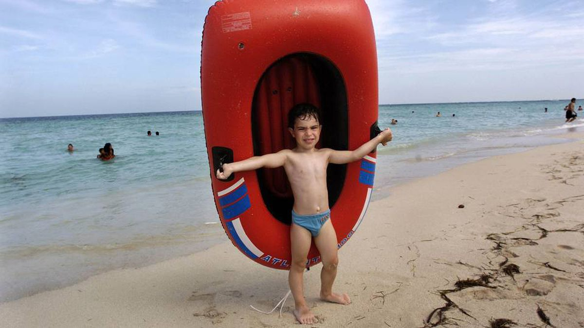 A three-year-old hits the beach in style.