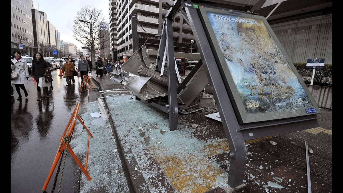 People walk by a ruined bus stop which was crushed by part of fallen outer wall of a nearby building in Sendai, Miyagi prefecture, Japan.