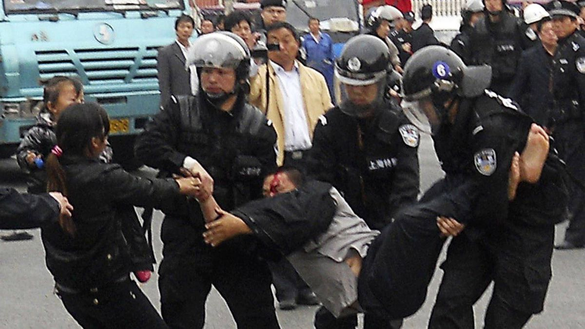 Policemen take away a truck driver and his wife holding their child in Shanghai April 21, 2011. Container truck drivers protested on Wednesday and Thursday in Shanghai over rising costs and surcharges, drivers and bystanders said.
