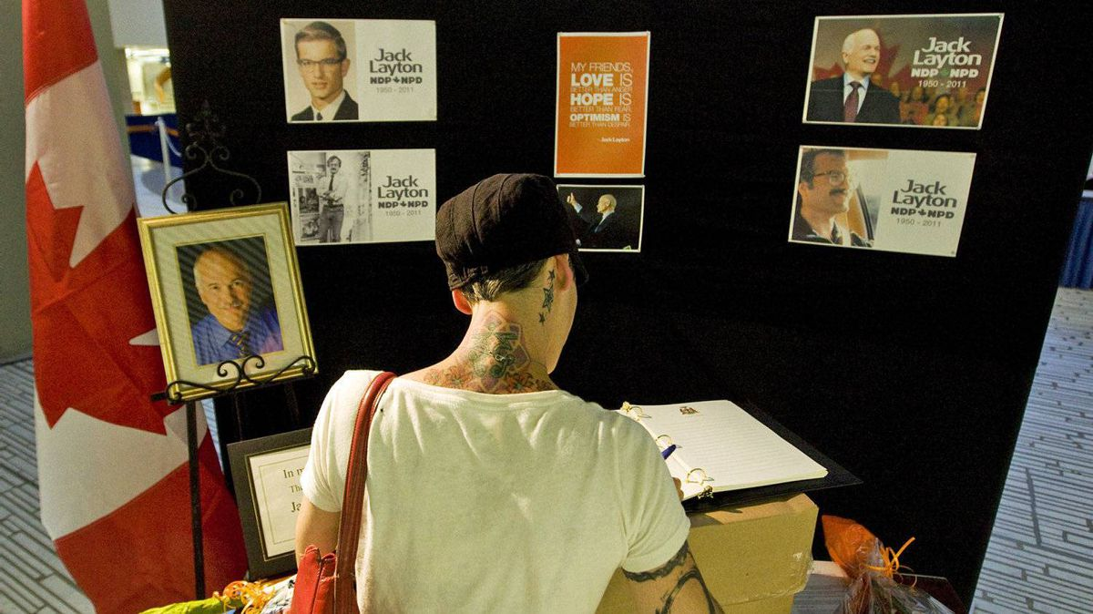 A Toronto resident signs a condolence book for late NDP leader Jack Layton at city hall on Aug. 22, 2011.