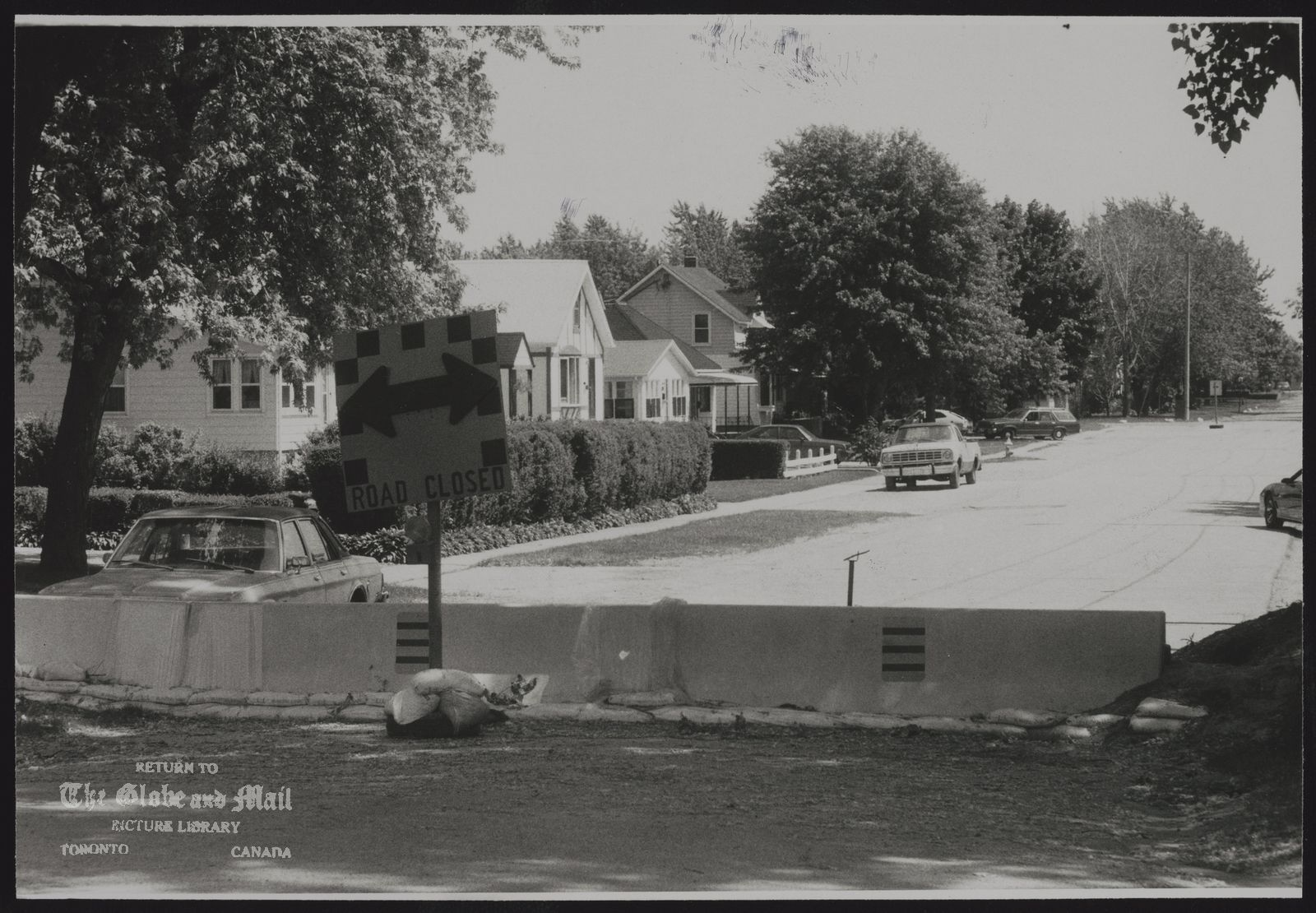 The notes transcribed from the back of this photograph are as follows: Barriers and sandbags set up as secondary flood wall around a Windsor subdivision.