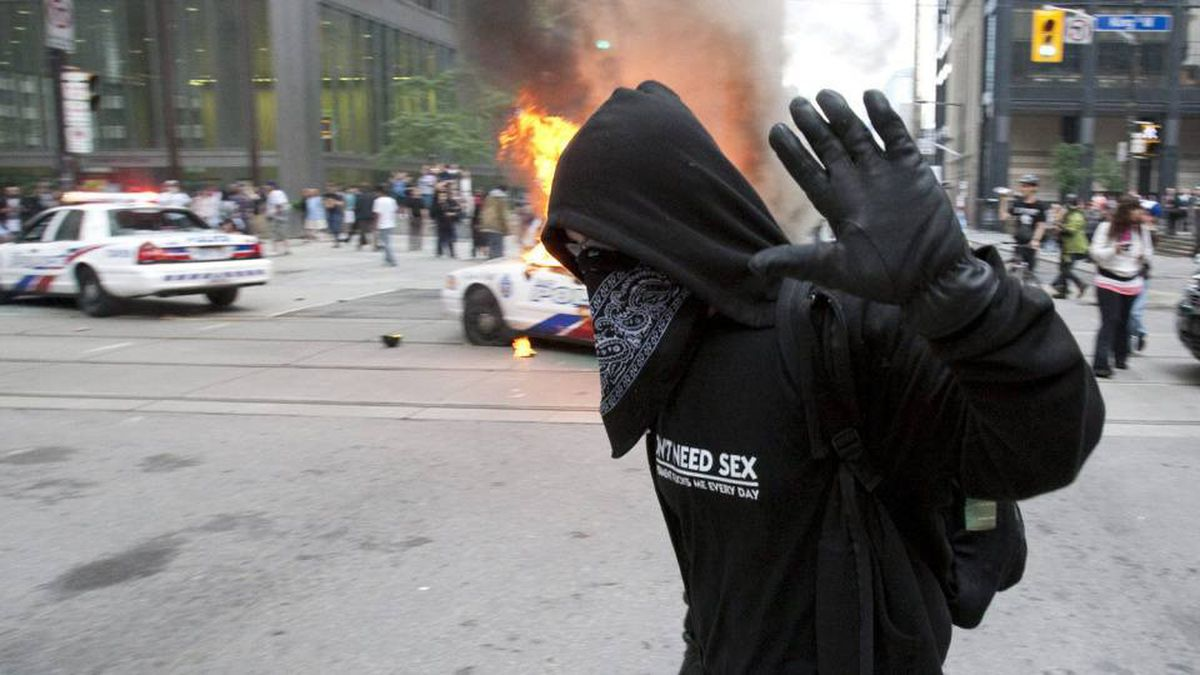 A G20 protester passes a burning police cruiser in downtown Toronto on June 26.
