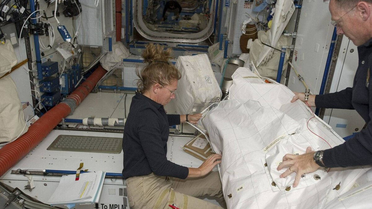 NASA astronaut Sandy Magnus (L) and space shuttle Atlantis Commander Chris Ferguson move supplies and equipment inside Node 2 or or the Harmony module of the International Space Station on July 11, 2011.