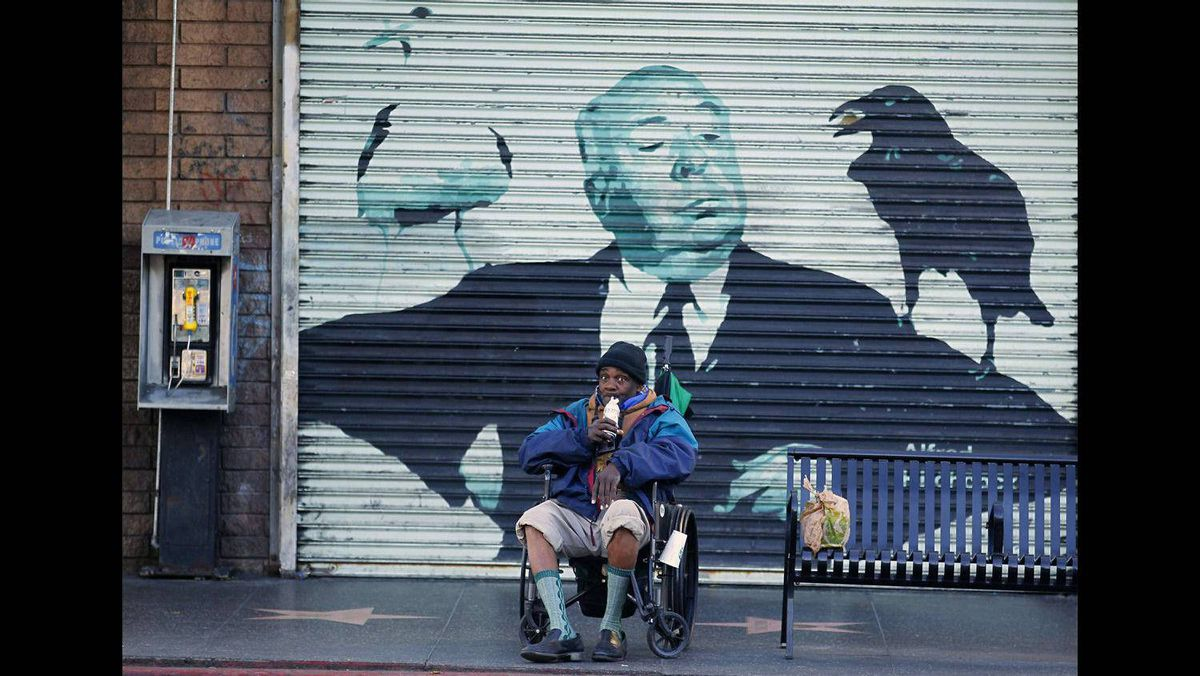 Store front metal doors on Hollywood boulevard depict the image of film director Alfred Hitchcock as a man in a wheelchair sips on a drink in Hollywood, California February 22, 2012.