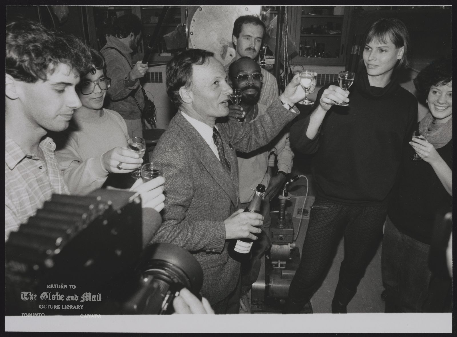 John POLANYI Toronto. Chemist John Polanyi 's chemistry students salute him with champagne after learning he had won Nobel Prize for chemistry.