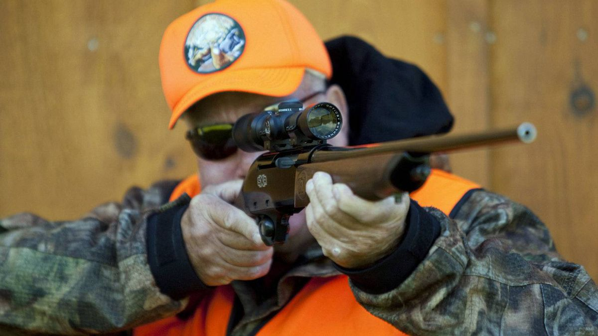 A rifle owner checks takes aim at a hunting camp near Ottawa on Sept. 15, 2010.