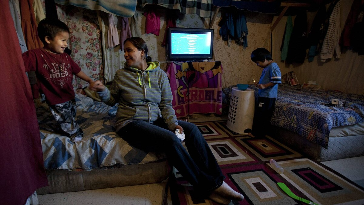 Lisa Linklater plays with her sons Keilyn and Drisdyn in a temporary shelter in Attawapiskat, Ont., on Tuesday.