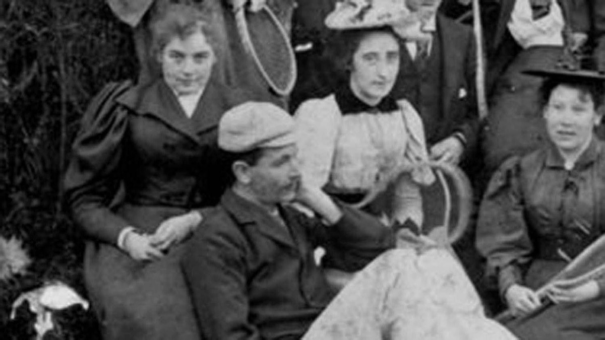 Detail of a photo of the artist Emily Carr at a tennis party. Carr is on the far left, with her mystery man leaning against her legs.