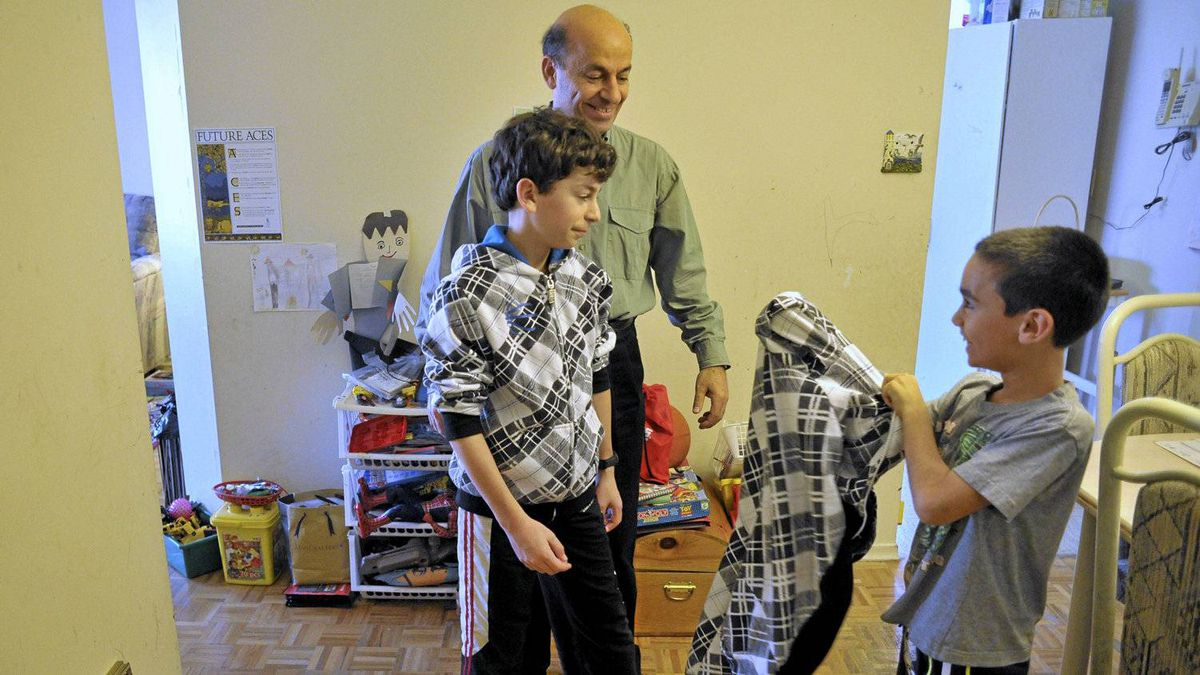 Rony Sehayek, an IT specialist who's been out of work for a year and his sons, Dan, left, and Matthew pose get dressed for photos in their Brampton apartment, October 20, 2010. Sehayek can no longer afford to put his boys through karate lessons.