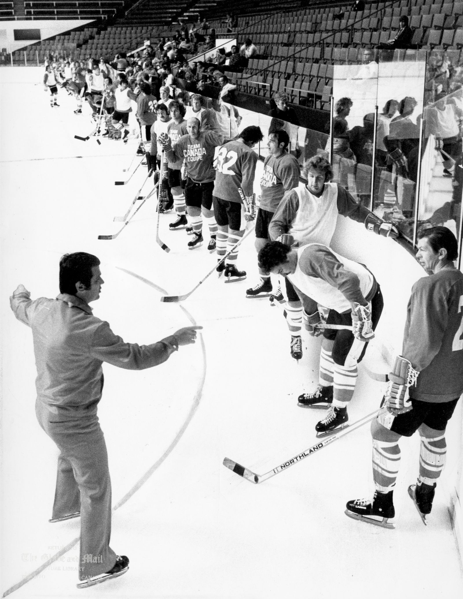 AUGUST 14, 1972 -- TORONTO -- TEAM CANADA TRAINING CAMP -- Team Canada players gather by boards in order to listen to head coach, Harry Sinden, during first practice session at Maple Leaf Gardens in Toronto on August 14, 1972. Long line of players starts with Team Canada co-captain, Stan Mikita at right in foreground. Series against Russia starts Sept. 2, 1972 in Montreal. Photo by Barrie Davis / The Globe and Mail. Originally published August 15, 1972.