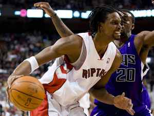 Toronto Raptors forward Chris Bosh, left, drives against Sacramento Kings defender Donte Greene during the first half of their NBA basketball game in Toronto, February 7, 2010.