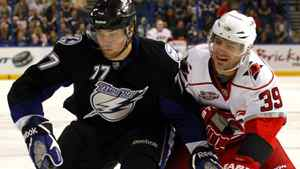 Tampa Bay Lightning's Victor Hedman, left, of Sweden, and Carolina Hurricanes' Patrick Dwyer battle for the puck during the first period of an NHL hockey game on Friday, March 25, 2011, in Tampa, Fla. The Hurricanes won 4-3.
