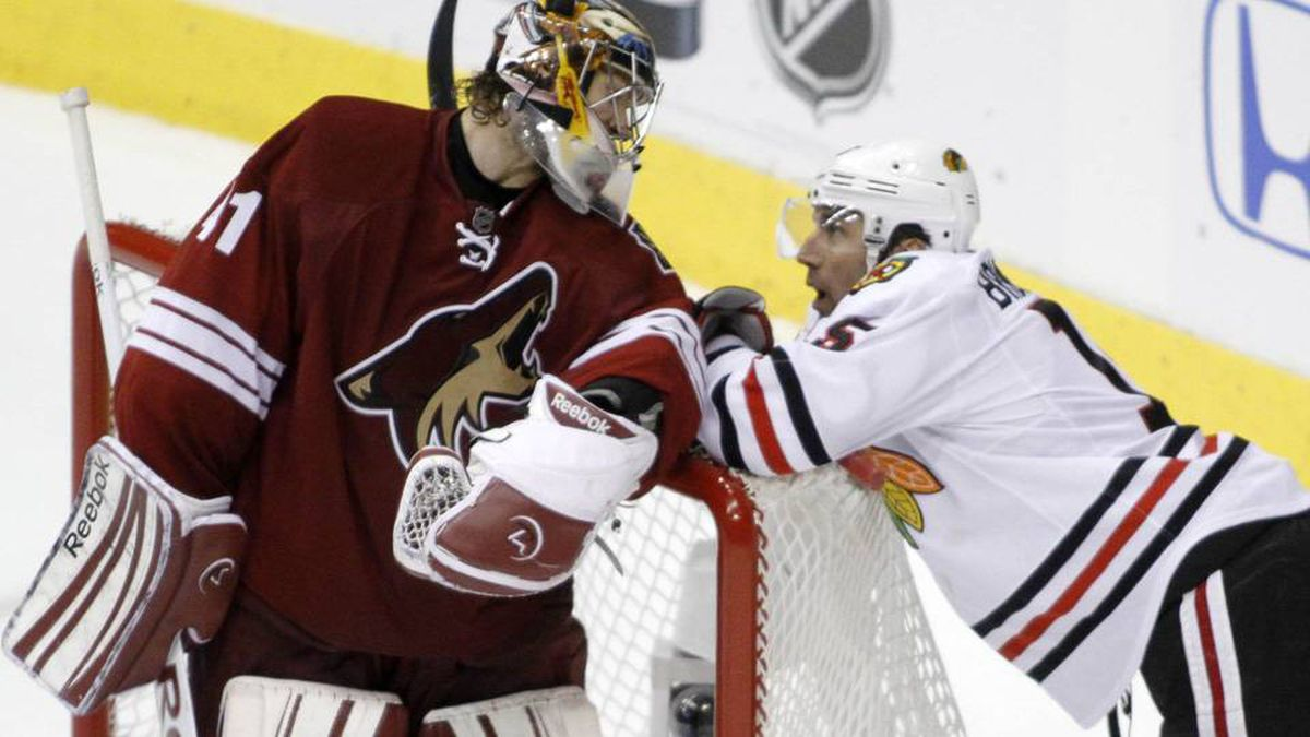 Chicago Blackhawks left wing Andrew Brunette (15) shares words with Phoenix Coyotes goalie Mike Smith (41) after his scoring chance was stopped by Brunette in the 2nd period during Game 2 of the NHL Western Conference quarter-final hockey playoffs in Glendale, Ariz.