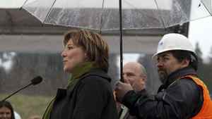 Construction worker Howard Bassett holds an umbrella over B.C. Premier Christy Clark during her announcement of the 50 per-cent completion of the South Fraser perimeter road in Surrey, British Columbia, April 3, 2012.