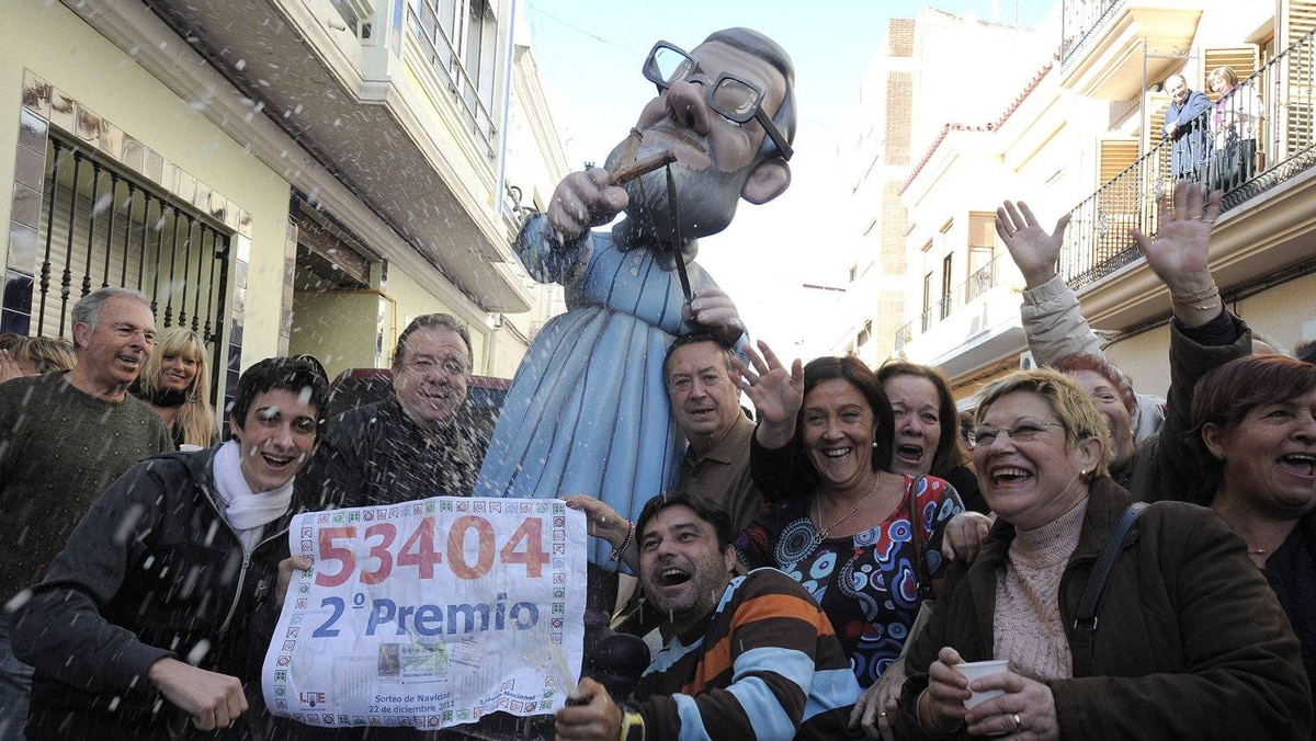 A crowd celebrates Thursday after winning second prize in Spain's Christmas lottery 'El Gordo' (the Fat One) in Manises, near Valencia. Crisis-hit Spaniards bought a record number of tickets to make this El Gordo the richest ever with $3.3-billion in prizes split amongst thousands of winners.