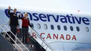 Conservative leader and Canada's Prime Minister Stephen Harper waves as he boards his campaign plane with his wife Laureen in Ottawa April 3, 2011. Canadians will head to the polls in a federal election May 2.
