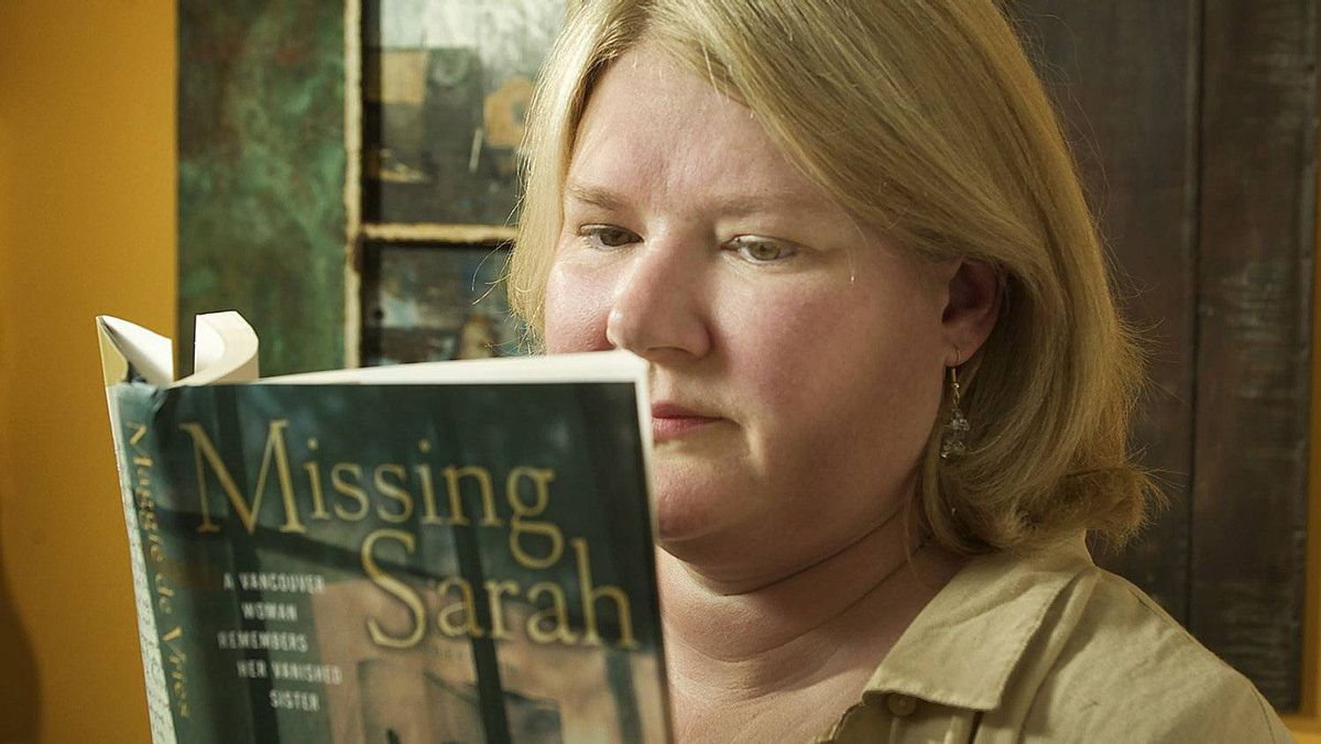 Maggie De Vries holds up the book she wrote about her sister Sarah de Vries who went missing on April 14, 1998.