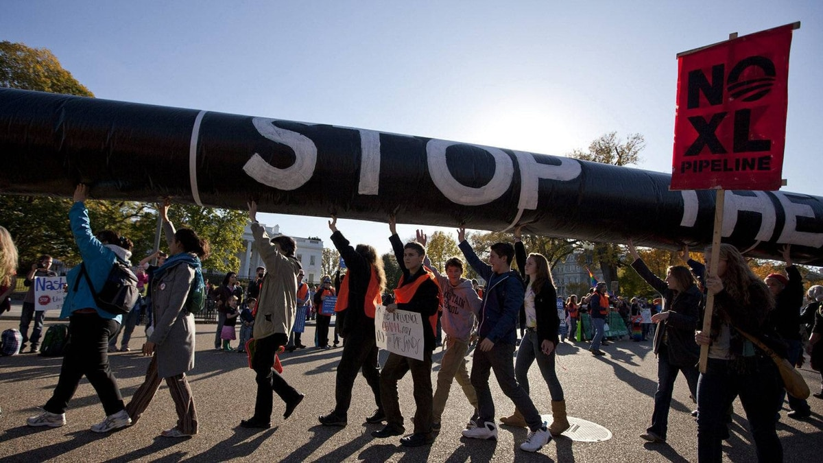 Demonstrators march with a replica of a pipeline during a protest against the Keystone XL pipeline Sunday outside the White House in Washington.