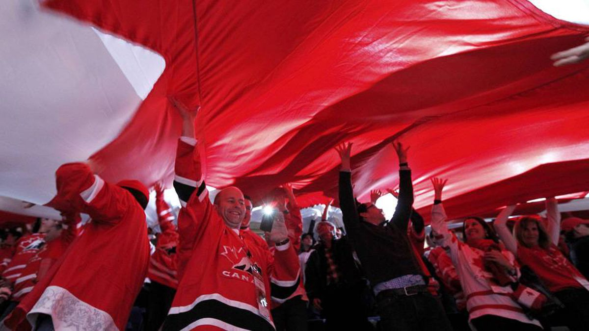 Canada fans hold up a giant flag during the first period of play in the bronze medal game of the 2012 IIHF U20 World Junior Hockey Championship in Calgary.