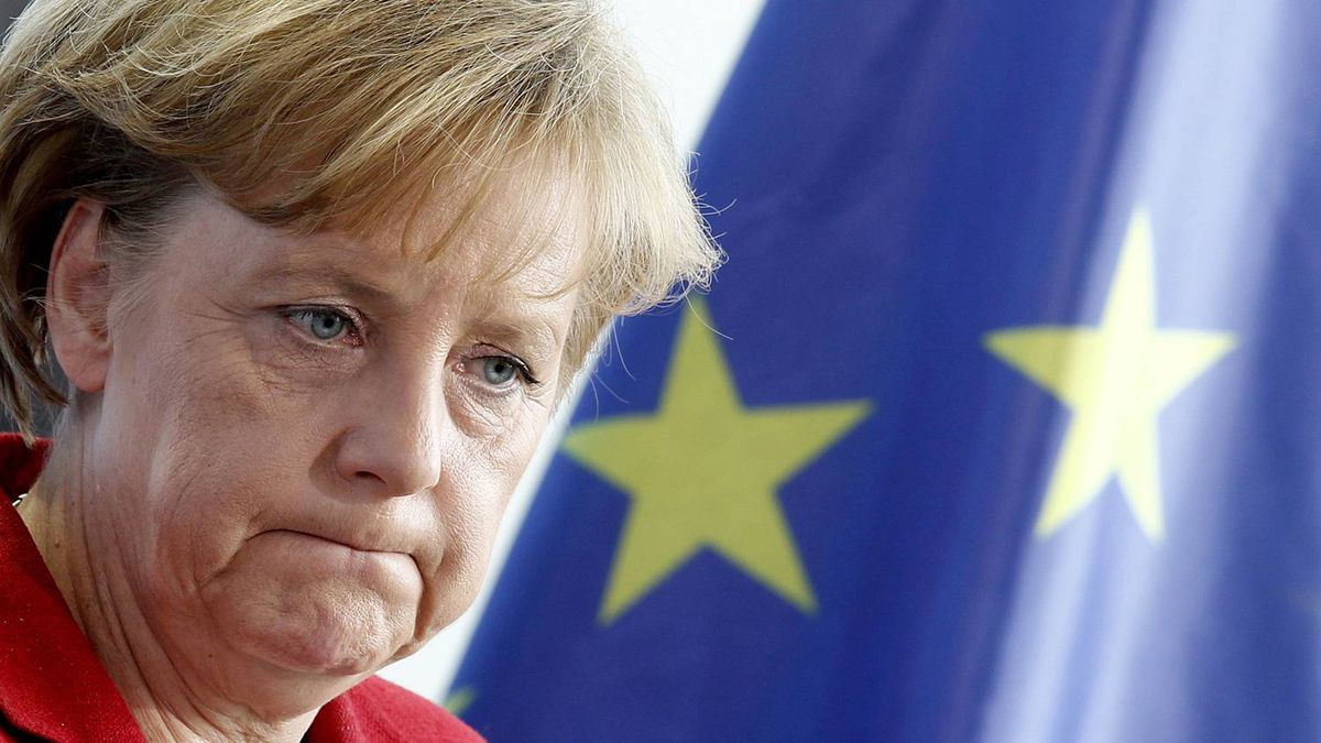 German Chancellor Angela Merkel stands in front of European Union flag