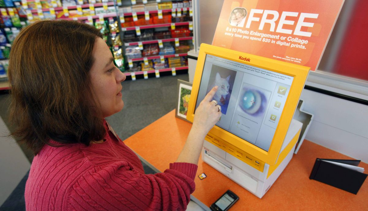 In this Sept. 16, 2010 photo, CVS manager Shanlee Carey poses for a photo demonstrating a Kodak kiosk in East Amherst, N.Y. Kodak has more than 100,000 kiosks installed at retail businesses worldwide.