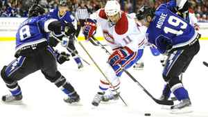 Montreal Canadiens' Scott Gomez (11) controls the puck against the Tampa Bay Lightning's Randy Jones (8) and Dominic Moore (19) during the first period of an NHL hockey game Saturday, March 5, 2011, in Tampa, Fla. The Canadiens won 4-2. (AP Photo/Brian Blanco)