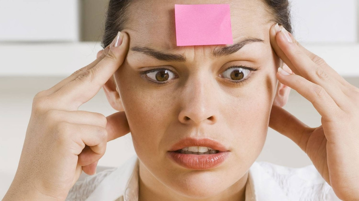 Businesswoman with sticky note on forehead