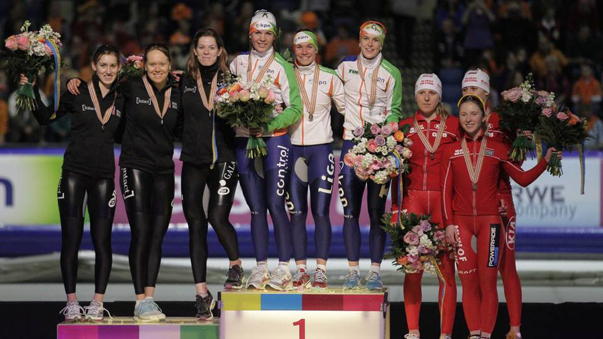 Winning team Netherlands, centre, team Canada, second place, and team Poland, third place, pose after the women's team pursuit at the World Single Distances Speed Skating Championships at Thialf stadium in Heerenveen, Netherlands, Sunday.