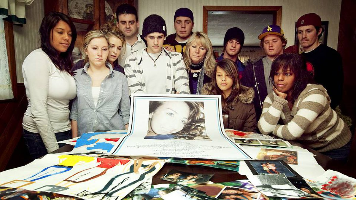 Friends and family of Reilly Anzovino stand behind photos and drawings of Reilly in her family's kitchen on Jan. 16, 2009.