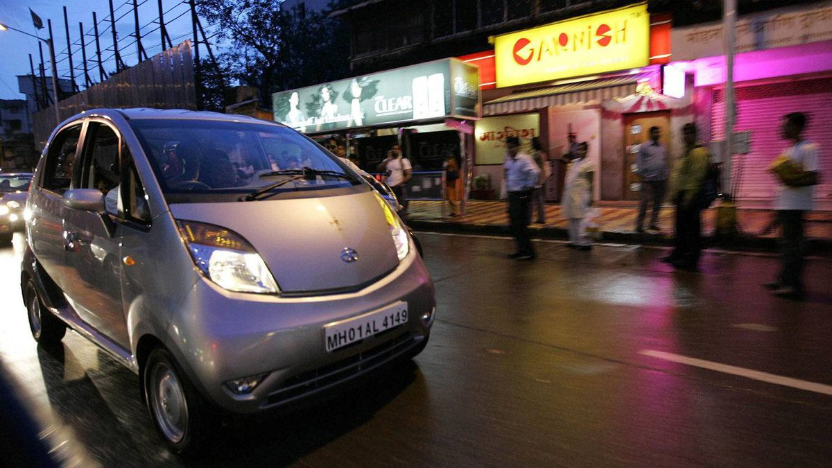 Pedestrians watch the first Tata Nano car being driven on the road in Mumbai, India, Friday, July 17, 2009.