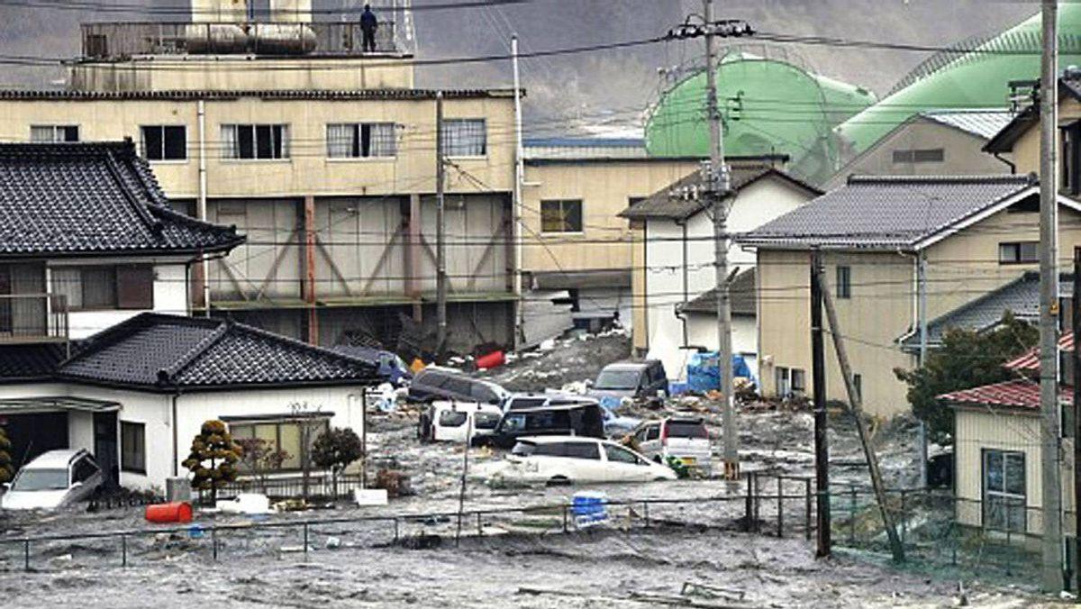 An earthquake-triggered tsunami washes away a warehouse and vehicles in Kesennuma, Miyagi prefecture, Japan, Friday March 11, 2011.