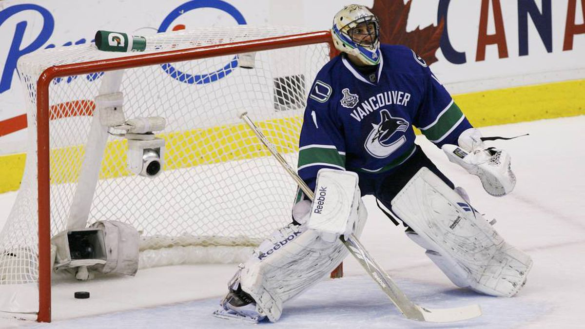 The puck sits in the net behind Vancouver Canucks goalie Roberto Luongo on a goal by Boston Bruins' Patrice Bergeron in the first period.