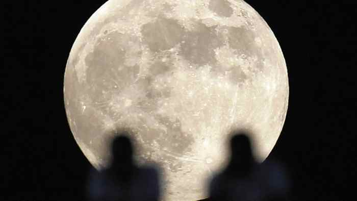 Fans watch the Egyptian Super Cup soccer match during a full moon at Cairo Stadium July 25, 2010.