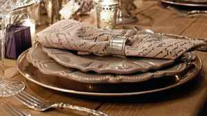 Warm, grey, scallop-edged dishes and linen napkins keeps the look quiet and understated.