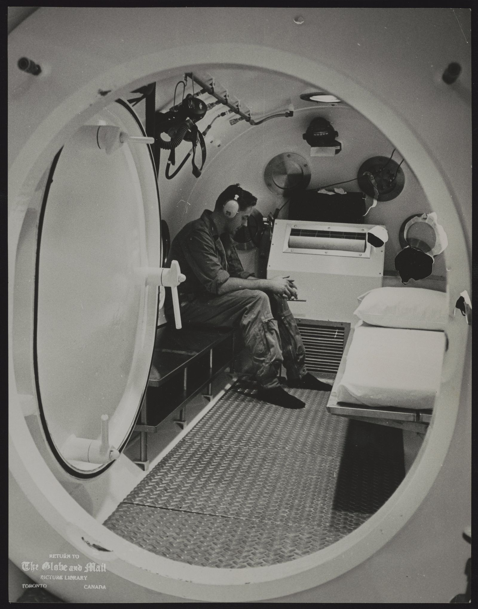 DECOMPRESSION CHAMBER Wesley Neihring, Royal Canadian Navy diver, demonstrates decompression chamber, 18 feet long, only one in Ontario. It was put into operation yesterday at Toronto General Hospital for divers or tunnel workers, for research. $50,000 chamber to treat bends.