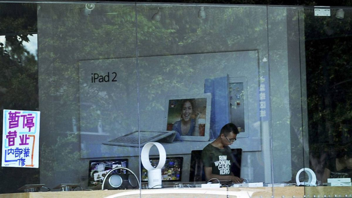 """A man works inside a shop masquerading as a bona fide Apple store while a notice displayed on a window reads """"Temporarily closed for internal renovation""""July 26, 2011."""