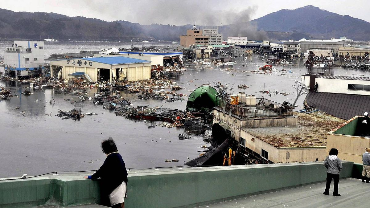 An earthquake-triggered tsunami washes away a warehouse and vehicles in Kesennuma, Miyagi prefecture, Japan, Friday March 11, 2011.