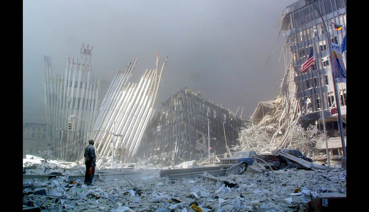A man stands in the rubble, and calls out asking if anyone needs help, after the collapse of the first World Trade Center Tower on Sept. 11, 2001, in New York.