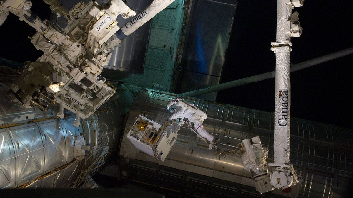 This NASA photo relealsed on July 18, 2011 shows astronaut Mike Fossum as he carries a Robotics Refueling Mission (RRM) payload from Atlantis' cargo bay to a platform used by the space station's famous robot DEXTRE. Pictured above on the far left, DEXTRE prepares to help move a failed space pump back to Atlantis.