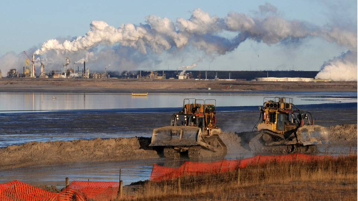 Heavy machinery works in a tailings pond at the Syncrude oil sands plant near Fort McMurray. Criticism of the energy-intensive oil sands has been relentless at the Copenhagen climate summit. Mark Ralston/AFP/Getty Images