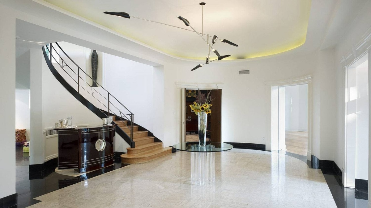 """In the restored foyer, all cove lighting was repaired, as was all plasterwork. """"Banks and banks of light switches were removed to visually simplify the space."""