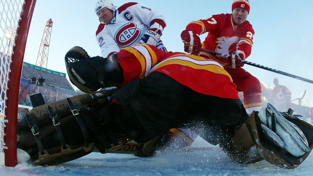 Goaltender Mike Vernon #30 and Brian MacLellan #27 of the Calgary Flames Alumni defend the net against Mike Keane #12 of the Montreal Canadiens Alumni during the Alumni game held as part of the 2011 NHL Heritage Classic festivities at McMahon Stadium on February 19, 2011 in Calgary, Alberta, Canada. (Photo by Andre Ringuette/Getty Images)