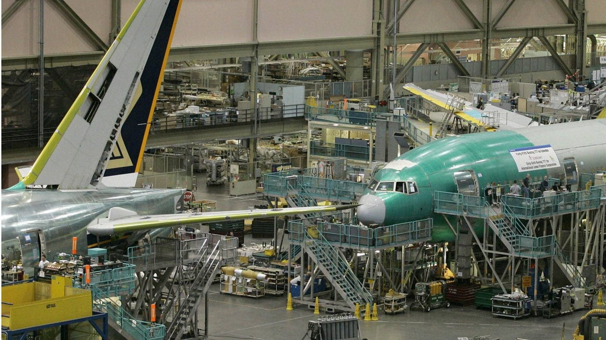 In this file photo, Boeing employees work on the 777 airplane assembly line.