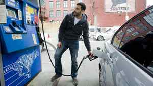 Mostafa Mahmood puts gas in his car in Montreal in April. High prices don't seem to have fazed Americans and Canadians planning their summer holidays.