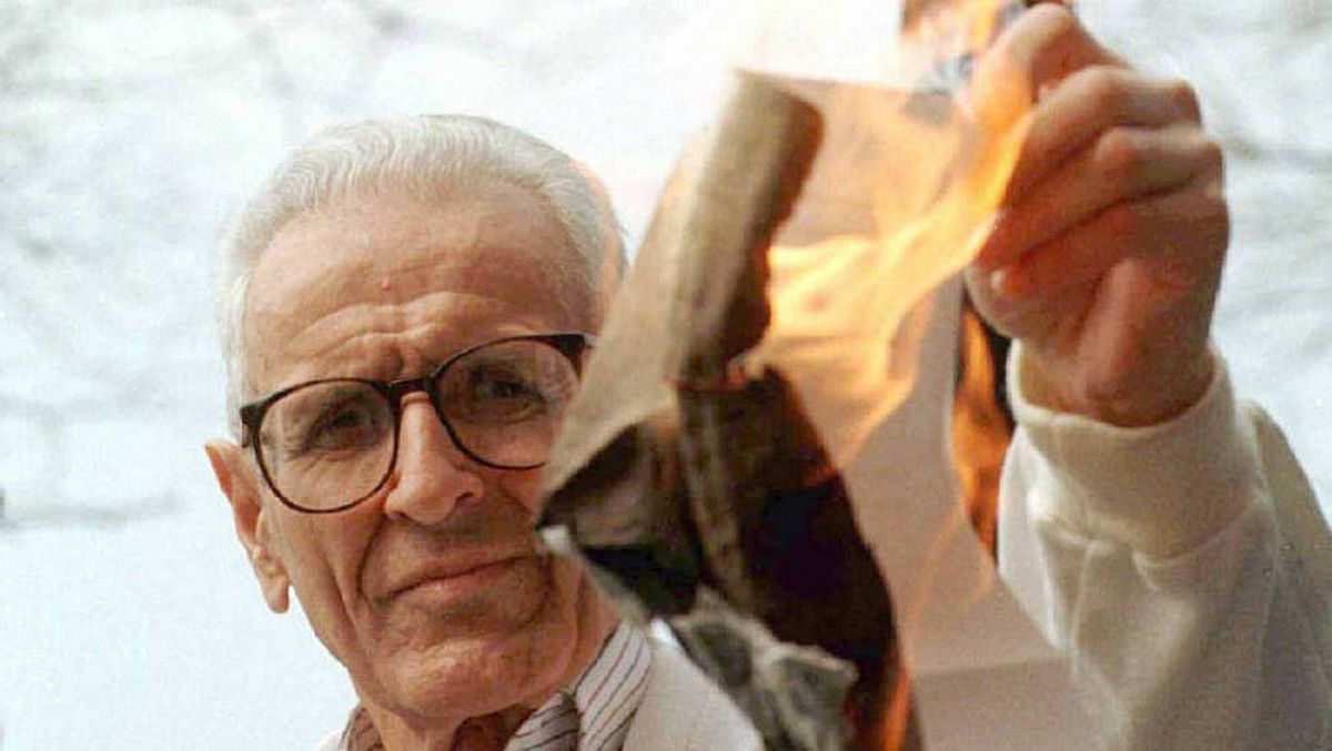 Dr. Jack Kevorkian burns a cease-and-desist order from the state of Michigan outside the state office building in Detroit Friday, April 4, 1997. The cease-and-desist order warns him to stop assisting in suicides or face charges of practicing medicine without a license. (AP Photo/Carlos Osorio)
